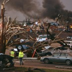 Emergency personnel walk through a neighbourhood severely damaged by a tornado near the Joplin Regional Medical Center in Joplin on 22 May, 2011. (AP Photo/Mark Schiefelbein/PA Images)