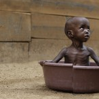 Two-year-old Aden Salaad looks up at his mother as she bathes him in a tub at a Doctors Without Borders hospital where Aden received treatment for malnutrition outside Dadaab, Kenya on 11 July, 2011. (AP Photo/Rebecca Blackwell/PA Images)