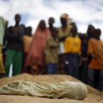 The shrouded body of 12-month-old Liin Muhumed Surow lays before burial at UNHCR's Ifo Extention camp outside Dadaab, Eastern Kenya, 100 km from the Somali border on 6 August, 2011. Liin died of malnutrition 25 days after reaching the camp, her father Mumumed said. The drought and famine in the horn of Africa killed more than 29,000 children under the age of 5 in 90 days in southern Somalia alone over the summer, according to US estimates. (AP Photo/Jerome Delay/PA Images)