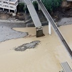 Photo taken from a Kyodo News helicopter on 5 September showing a bridge over the Kumano River in Totsukawa, Nara Prefecture, Japan after it was severed in flooding caused by Typhoon Talas. (Kyodo/PA Images)