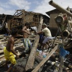 Residents slowly rebuild homes which were wiped out by strong currents from recent typhoons along a coastal village in Tangos, Navotas city, north of Manila, Philippines on 3 October, 2011. (AP Photo/Aaron Favila/PA Images)