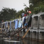 Thai flood victims use concrete blocks that were to be used in the construction of an elevated railway as temporary shelters in a flooded neighbourhood on the outskirts of Bangkok on 10 November, 2011. (AP Photo/Altaf Qadri/PA Images)