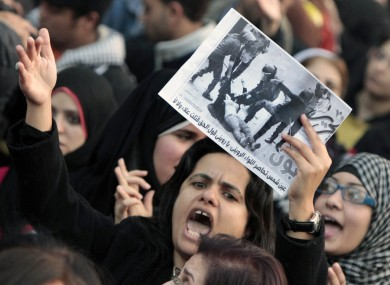 An Egyptian woman raises a copy of Al Tahrir newspaper fronted by a picture showing half naked woman protester beaten by army soldiers