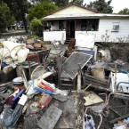 Mud-caked debris is piled in front of a house at Condamine, Australia, after floodwater washed away or ruined hundreds of homes in January 2011. (AP Photo/Dean Saffron/PA Images)