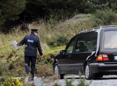 A garda directs a hearse at the scene of the body's discovery yesterday.