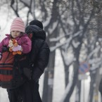 A child is carried by its father in a backpack on a cold winters day in Sofia. (AP Photo/Valentina Petrova/PA Images)