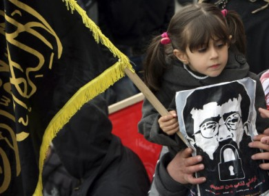 Maali Adnan, 4, holds a picture of her father during a recent solidarity protest in Arrabeh, the West Bank.