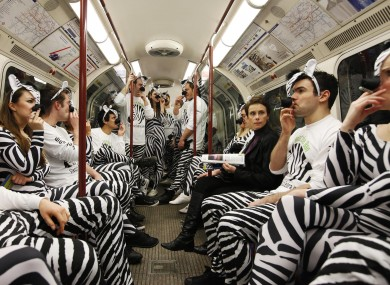 People dressed as zebras 'smoke' on the London Underground to promote the launch of the Zebra Electric Cigarette.