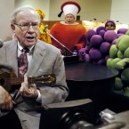 Berkshire Hathaway chairman Warren Buffett plays the ukelele at the Fruit of the Loom stand at the Qwest Center in Omaha, Nebraska. He has given instruments and lessons to children's clubs and auctioned one of his ukeleles for charity for $11k. (Pic: AP Photo/Nati Harnik)