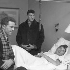 Manchester United footballers Harry Gregg, left, and Billy Foulkes, talk with teammate Ken Morgan in hospital.