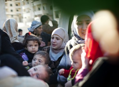 A family leaves their house after the building was hit by a Syrian army tank in Idlib, north Syria on Sunday.