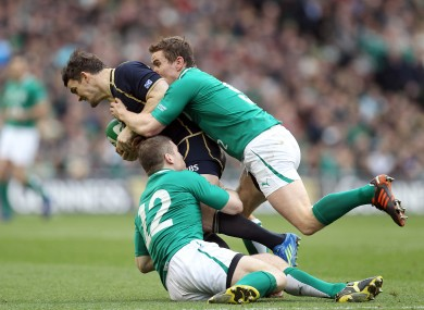 Ireland's Gordon D'Arcy and Eoin Reddan tackle Max Evans of Scotland.