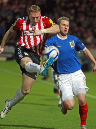 Derry's Stewart Greacen sees off the challenge of Linfield's Peter Thompson at the Brandywell last night.