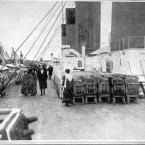 Passengers take the air on deck of the Titanic - passing by the lifeboats, of which there were too few to accommodate everyone when the ship sank.