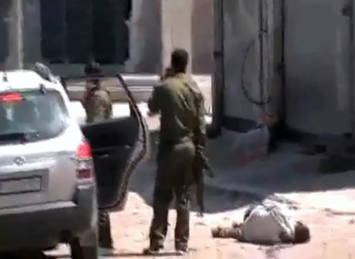 This image made from amateur video and released by Syrian Media Centre Friday, April 13, 2012 purports to show a dead body next to Syrian soldiers in Daraa, Syria