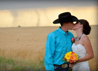 Caleb & Candra Pence pose for a wedding photo as a tornado swirls in the background