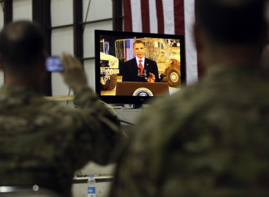 Military personnel watch on a screen as President Barack Obama makes a live address at Bagram Air Base