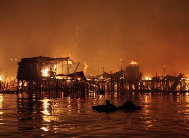 A man floats in the water as his neighbourhood - houses on stilts on the edge of a bay - went up in flames in Manila, the Philippines capital.