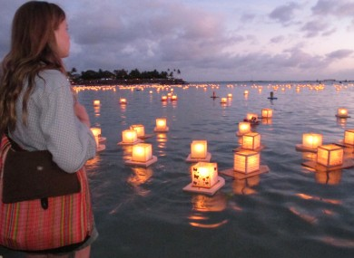 Julia Douglas, 18, of Honolulu, watches lanterns float by at an annual ceremony in Hawaii to commemorate loved ones.