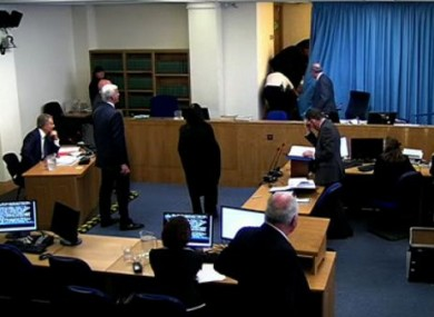 The protester (centre) is bundled from the room. Tony Blair can be seen seated at the left hand side of the room