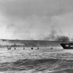 Under the cover of naval shell fire, American infantrymen wade ashore from their landing craft during the initial Normandy landing operations in France. (AP Photo/Peter Carroll)