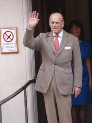The Duke of Edinburgh waves as he leaves the Central London hospital this morning.