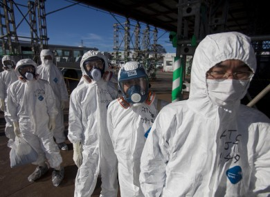 Workers in protective suits and masks wait to enter the emergency operation center at the crippled Fukushima Dai-ichi nuclear power station