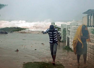 Residents evacuate their home as waves crash in the Caribbean Terrace neighborhood of eastern Kingston, Jamaica on Wednesday