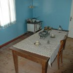A small stove and delicate tablecloth remain intact for visitors to see. (Wikimedia Commons)