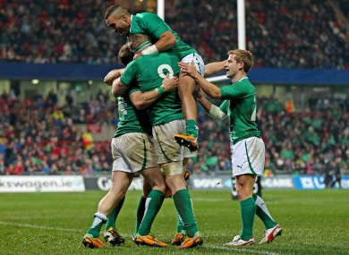 Simon Zebo leaps onto a mob of celebrating Irish players.