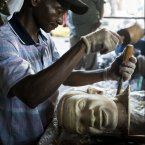 A woodcarver in Mwenge uses the wood to carve a bust.