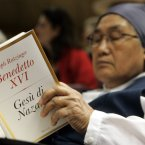 A nun leafs through an Italian edition of Pope Benedict XVI's first book