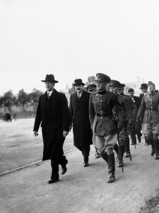 Éamon de Valera, left, and Frank Aiken, Minister for Defence being escorted by officers of the Free State Army, on the former's arrival on Spike Island, on 11 July, 1938.