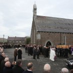 Large crowds gather outside the church in Ventry after the funeral of Páidí Ó Sé.