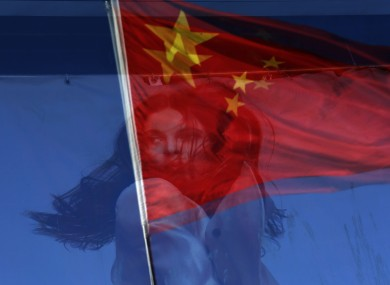 A Chinese national flag is reflected on a fashion poster at a shopping mall in Beijing, China