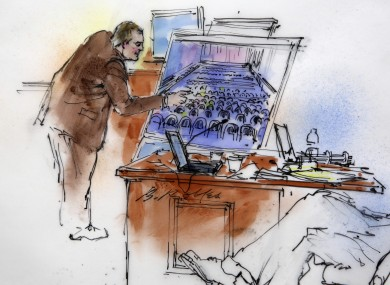 This courtroom sketch shows Aurora Police Detective Matthew Ingui pointing to a large photograph of the inside of the Century 16 theatre.