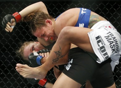 Liz Carmouche, top, grapples with Ronda Rousey during their UFC 157 women's bantamweight championship mixed martial arts match.