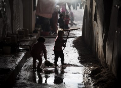 Syrian children play with cleaning tools at a camp for displaced people