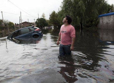 A man looks to the sky outside his home in a flooded street where a car is submerged in La Plata