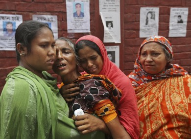 Bangladeshi relatives of missing workers in a building that collapsed on Wednesday comfort each other in Savar.