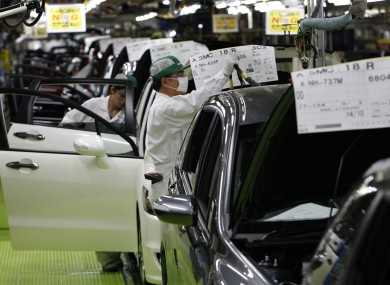 Workers check cars at a car factory north of Tokyo last year