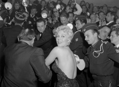 Kim Novak is hustled through the crowd of media to attend an evening performance at the Cannes Film Festival in 1956