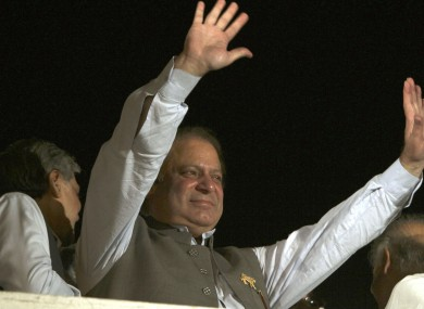 Nawaz Sharif waves to his supporters at a party office in Lahore last night