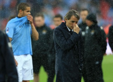 Manchester City manager Roberto Mancini stands on the pitch dejected after losing the FA Cup final.
