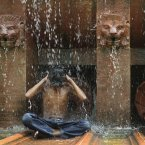 A young Indian boy enjoys bathing under a fountain near the India Gate monument to beat the heat on a hot day in New Delhi, India. Mercury rose in the national capital to around 44 degrees Celsius (111 degrees Fahrenheit) Thursday. (AP Photo/Tsering Topgyal)
