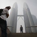 A tourist poses for a photo in front of Malaysia's landmark Petronas Twin Towers obscured in haze in Kuala Lumpur, Malaysia. (AP Photo/Vincent Thian)
