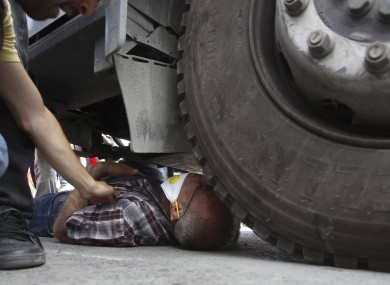 A protester lies under the wheel of a police water cannon vehicle.