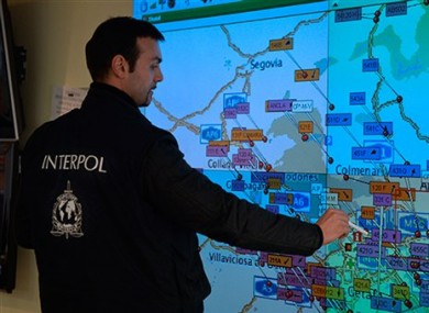 An Interpol officer looks at map where seizures have taken place