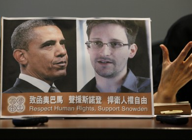A Chinese legislator holds a photograph of Barack Obama and Edward Snowden at a news conference in Hong Kong