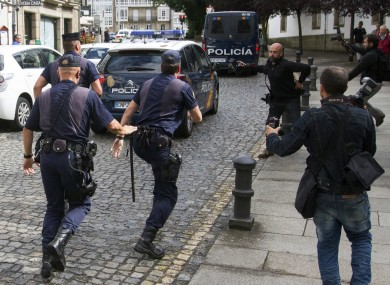 Media run after a police car carrying arrested train driver Francisco Jose Garzon Amo on Sunday